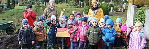 Kindergartenkinder pflanzen Wildstrauchhecke auf dem evangelischen Hauptfriedhof Braunschweig